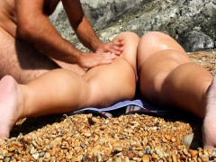 providing her a sensual rub in the beach